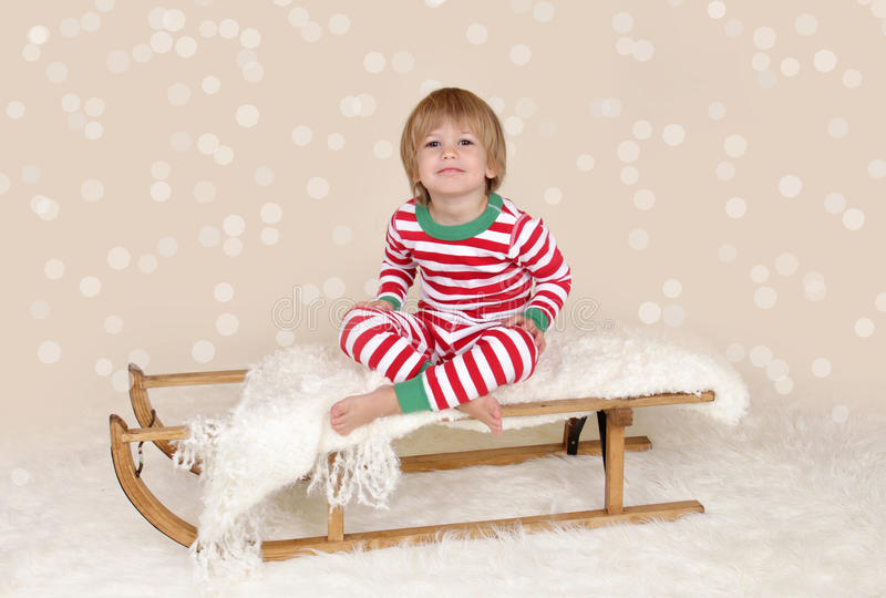 Winter Holidays: Laughing Happy Child in Christmas Pajamas Sled royalty free stock image