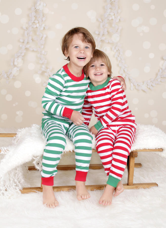 Winter Holidays: Laughing Happy Kids in Christmas Pajamas Sled i stock photography