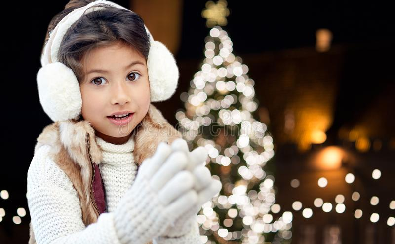 Happy girl wearing earmuffs over christmas lights stock photos