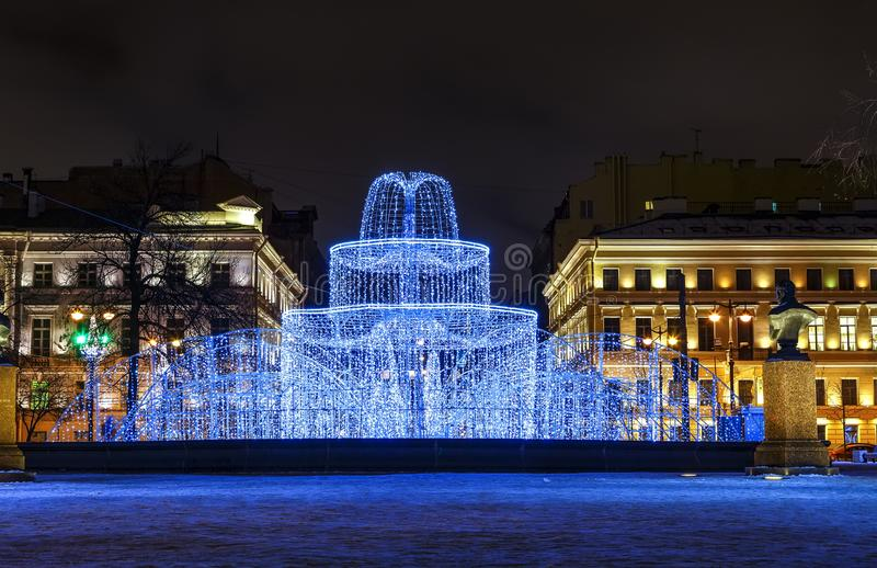 Winter holidays. Street Christmas decorations in the evening. Admiralty building, Winter fountain of hundreds of small lights in stock photo