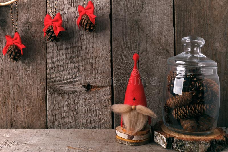 Winter home decor. Christmas rustic interior. Farmhouse decoration style. decorative gnome and a jar of cones. stock photo