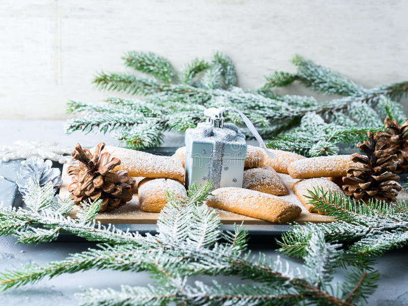Winter home made cookies for Christmas. Home made cookies for Christmas with icing sugar. Winter sweet baked food still life. Snow on fir tree branches stock images