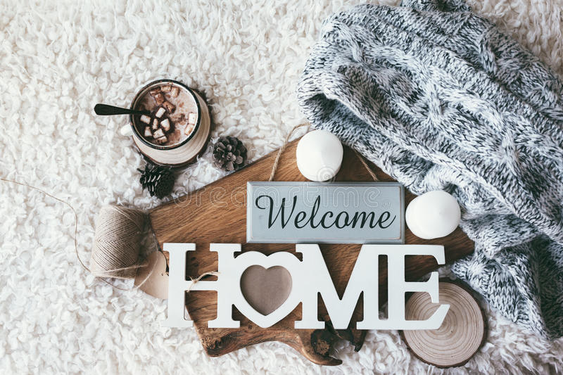 Winter homely decor. Winter homely scene, scandinavian style. Warm knit sweater, candles, cup of sweet cocoa with marshmallows and other decor on tray in bed stock photo