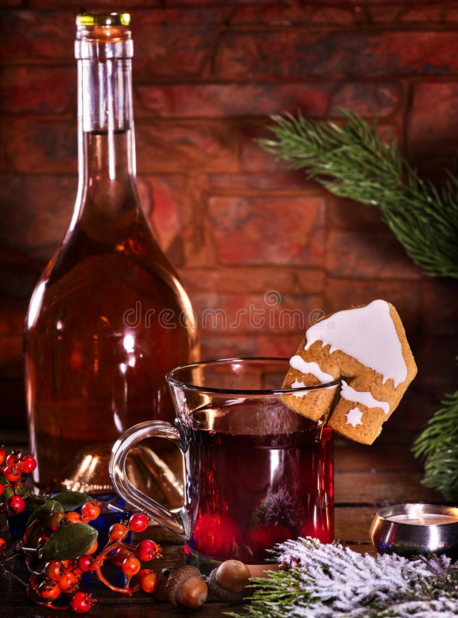 Winter hot drink with cookie and bottle of wine. Still life of winter hot drink with bottle of red wine . Warming mulled wine with cookie in form of house on stock photo