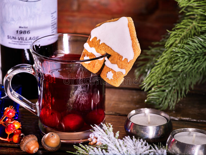 Winter hot drink with cookie and bottle of wine. Still life of warming drink with bottle of red wine . Label on bottle of wine. Warming mulled wine with cookie stock images
