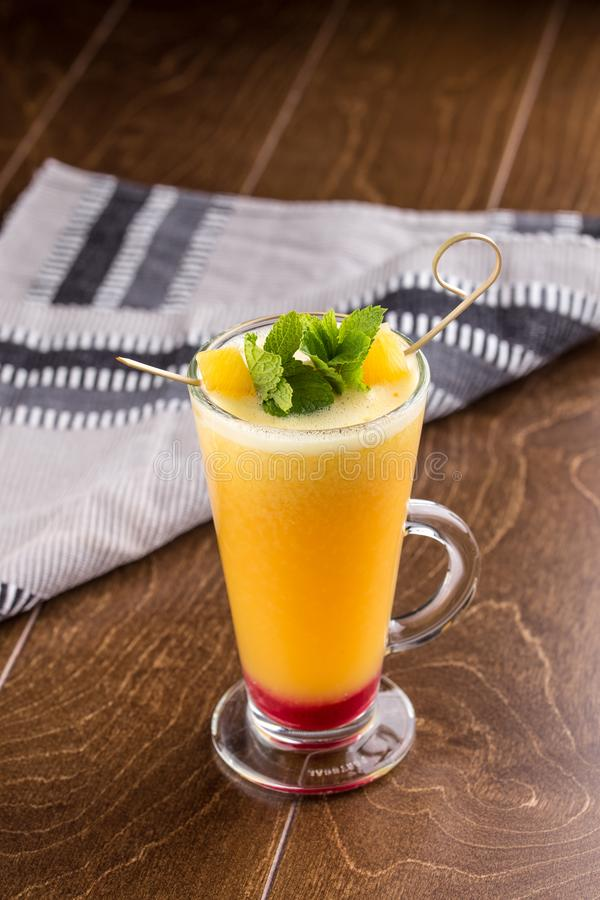Winter hot drink from oranges and berries in tall glass on wooden table royalty free stock photography