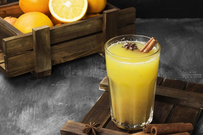 Winter hot drink from oranges and spices on a black background. royalty free stock photography