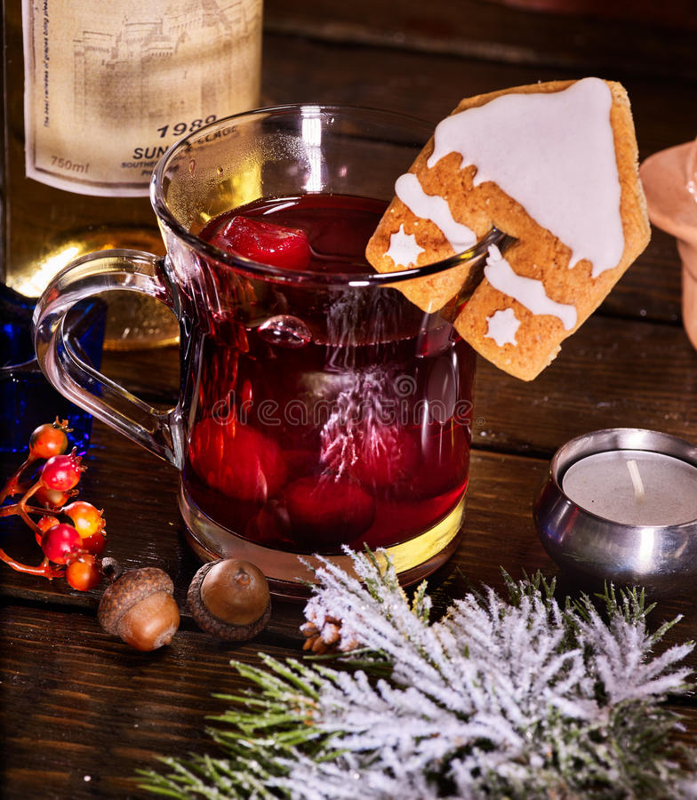 Winter hot smoking bishop drink with cookie and bottle wine. Close up of glass mug of warming smoking bishop drink with bottle of wine . Label on bottle of wine royalty free stock images
