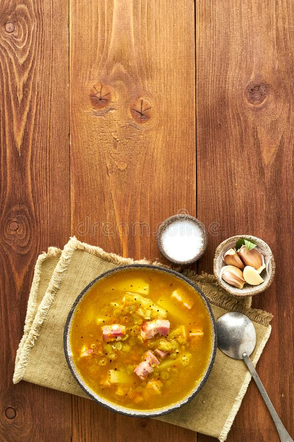 Winter hot soup with chopped green peas, pork, bacon, smoked on dark brown wooden table. Delicious appetizing fat rich soup stock images