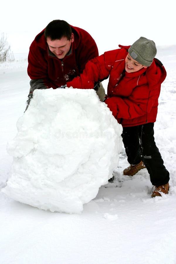 Winter - Huge Snowball. Man and boy making a snowman