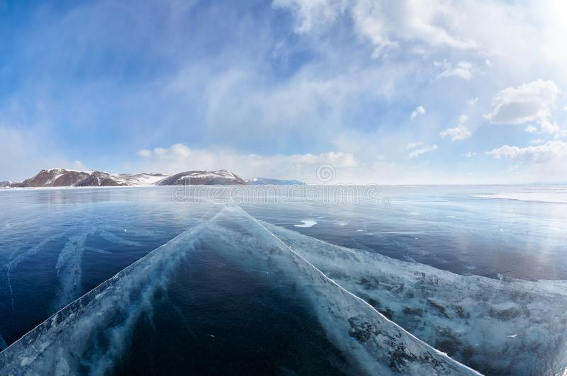 Winter ice landscape on Siberian lake Baikal with clouds. Wide angle shot of winter ice landscape on Siberian lake Baikal with dramatic weather clouds on blue royalty free stock image