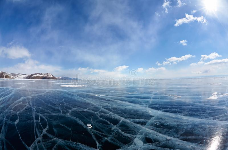 Winter ice landscape on Siberian lake Baikal with clouds. Wide angle shot of winter ice landscape on Siberian lake Baikal with dramatic weather clouds on blue stock images