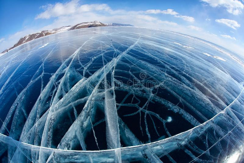Winter ice landscape on Siberian lake Baikal with clouds. Wide angle shot with fisheye lens of winter ice landscape on Siberian lake Baikal with dramatic weather royalty free stock images