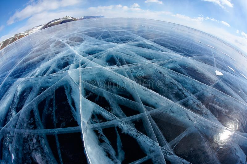 Winter ice landscape on Siberian lake Baikal with clouds. Wide angle shot with fisheye lens of winter ice landscape on Siberian lake Baikal with dramatic weather stock photography