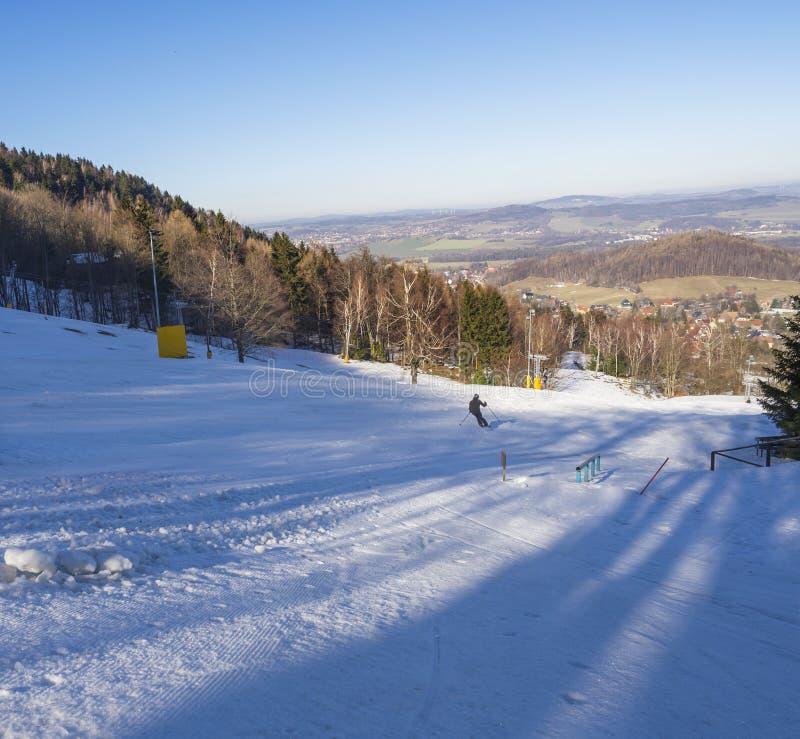 Winter im Skiort Lausche Waltersdorf in Deutschland mit einem Skifahrer und Vogelperspektive auf Dorf, später Nachmittag lizenzfreie stockbilder