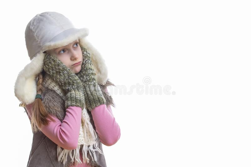 Winter Kids Fashion, Clothing And Holidays Ideas. Sad Looking Caucasian Girl In Pink Vest and White Winter Hat, Scarf and Mittens. Looking Upwards Over Pure stock image