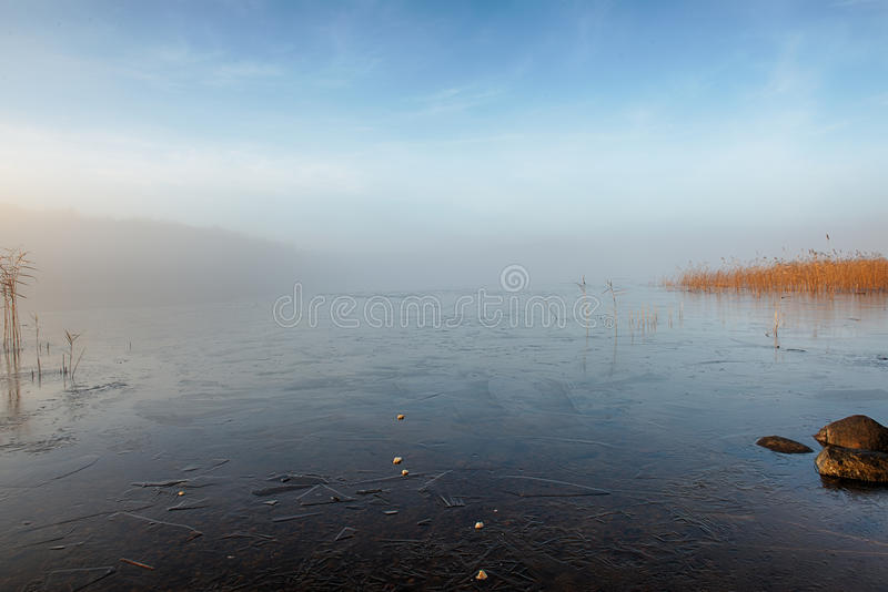 Winter lake in mist stock images