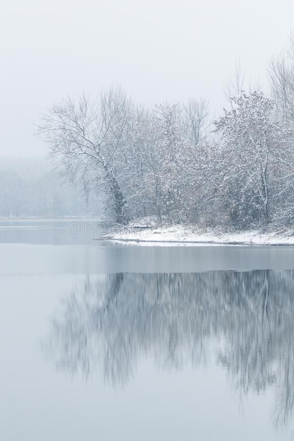 Winter lake scene reflecting in the water. Nature stock photos