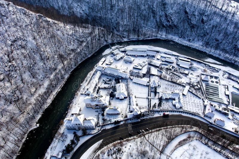 Winter landscape along a river valley in Romania with a view of Lainici Monastery from above. Aerial drone photo of a beautiful monastery in Romania set in a stock images