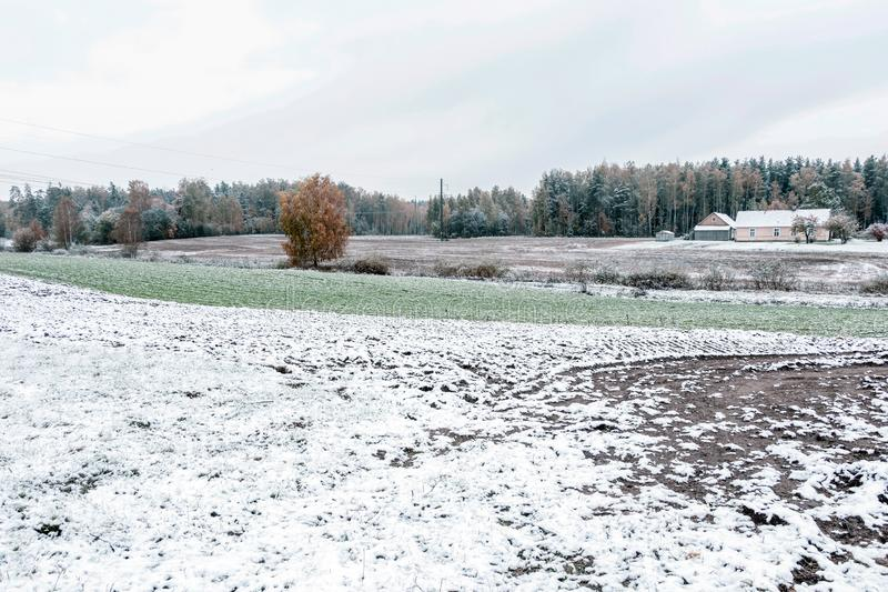 Winter landscape with first snow in the countryside fields with late autumn colors. Winter landscape with arable plowed field and first snow in the countryside royalty free stock photo