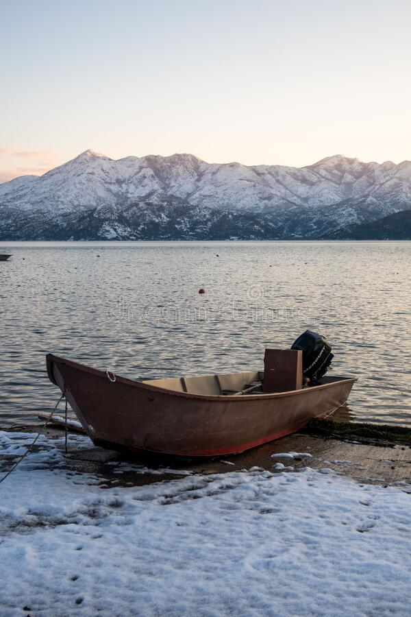 Winter landscape: boat on the shores of Lake Skadar, Montenegro. Boat on the shores of Lake Skadar, Montenegro. Snow-capped mountains background. Winter stock images