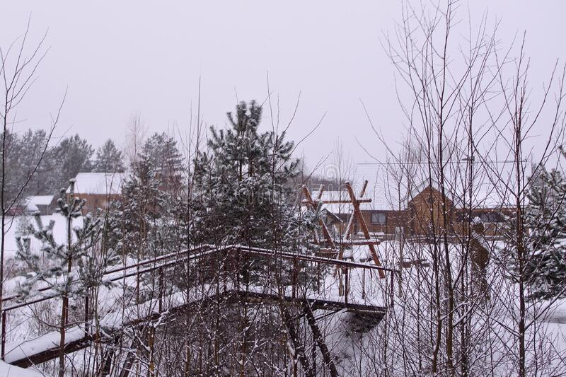 Hunting estate in the winter forest. winter landscape with bridge, trees and wooden house stock images