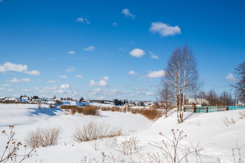 Winter landscape. Countryside. Lonely tree Frozen river. Sunny day. Blue sky. White clouds. royalty free stock photos