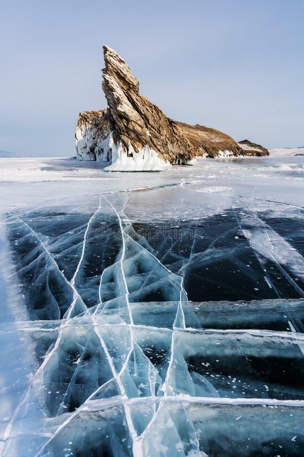 Winter landscape, cracked ground of frozen lake Baikal with beautiful mountain island on frozen lake royalty free stock photography