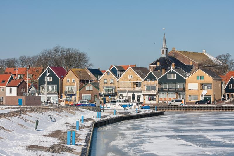 Snowy winter landscape Dutch fishing village Urk with frozen harbor. Winter landscape Dutch fishing village Urk with frozen harbor covered with snow royalty free stock photos