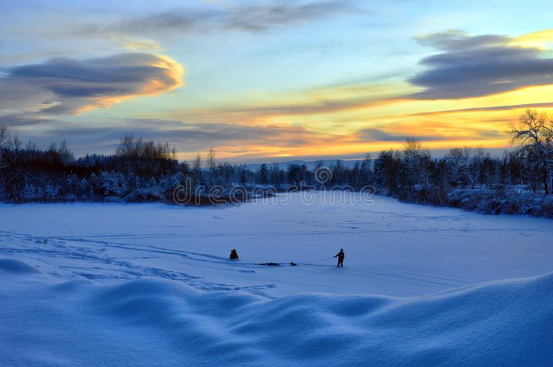 The winter landscape. Evening twilight. Children play in the snow. Winter fun. royalty free stock photo