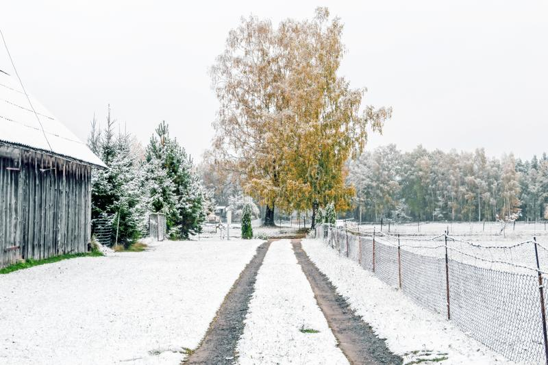 Winter landscape with first snow in the countryside fields with late autumn colors. Lonely empty road at winter landscape with first snow in the countryside royalty free stock photography