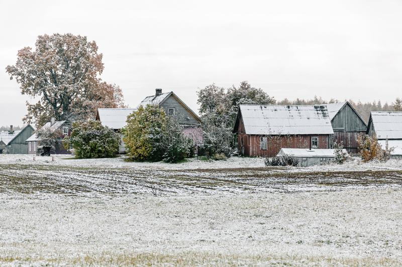 Winter landscape with first snow in the countryside fields with late autumn colors. Small houses at winter landscape with first snow in the countryside fields royalty free stock photos