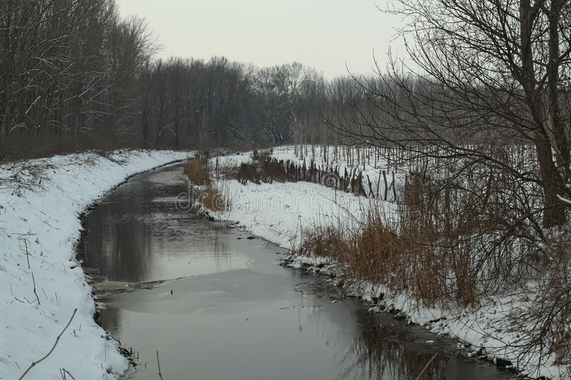 Winter landscape with frozen canal and snow all around.  stock image
