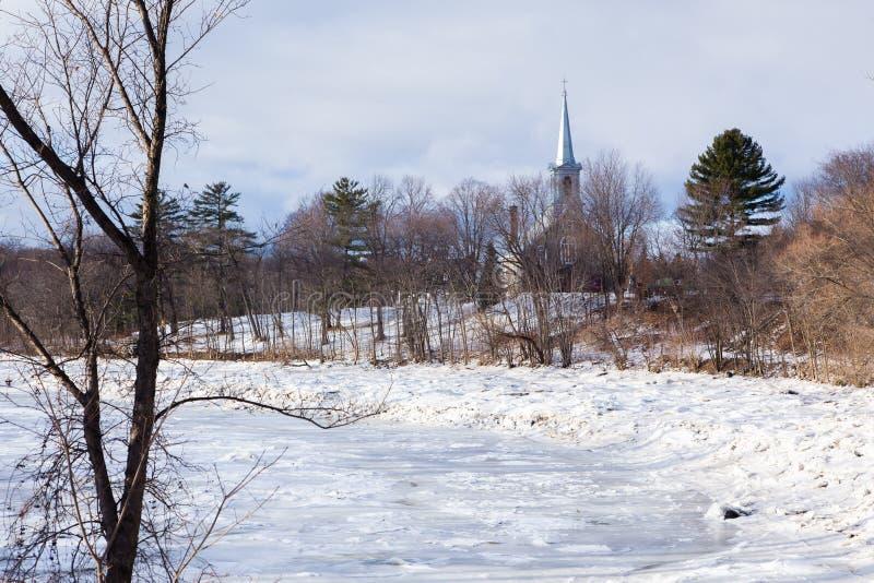 Winter landscape with frozen Cap-Rouge river and pretty small 1859 stone Saint-Felix-de-Valois church royalty free stock photos