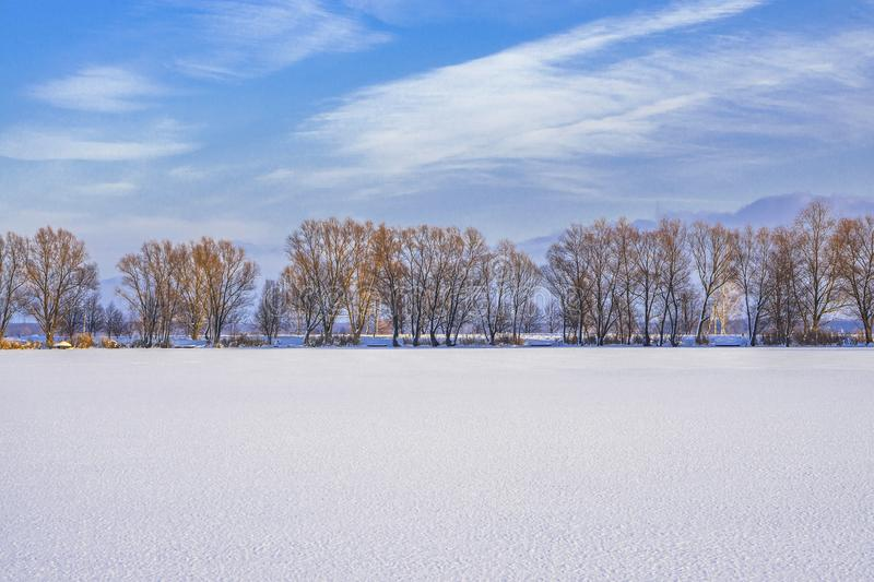 Winter landscape of frozen lake covered snow. Winter snowy landscape of frozen lake covered snow royalty free stock photo