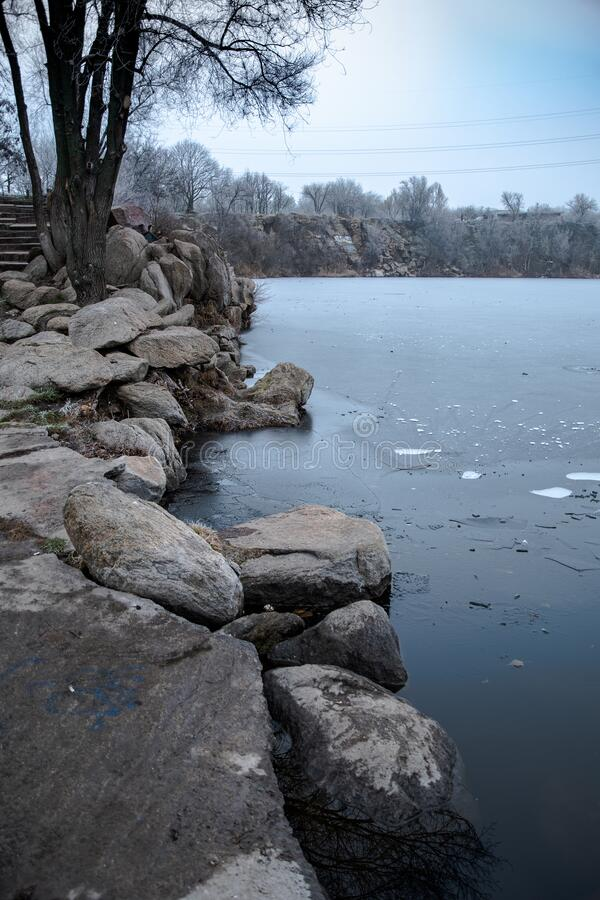 Winter landscape. Granite, rocky shore by the lake in a city park. Walk in the open air royalty free stock images