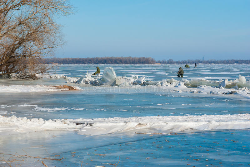 Winter landscape with hummocks and lonely fishermans on a Dnepr river. In Dnepropetrovsk city, Ukraine royalty free stock image