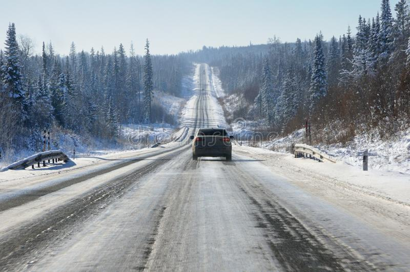 Winter landscape with icy tarmac road on the smooth hills covered with snowy forest in winter. In Siberia, Russia royalty free stock image