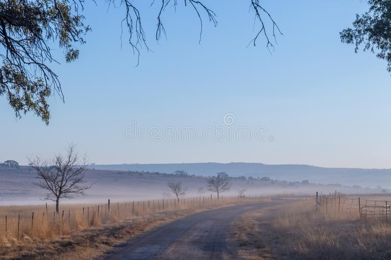 Winter landscape kwaZulu-Natal South Africa. Winter landscape with mist, dry trees, dry grass, fences and a dirt road image in landscape format stock images