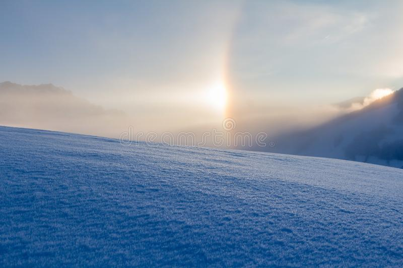 Snowy winter landscape in the alps, sunrise with halo phenomena. Winter landscape in the morning: Sunrise and halo phenomena, alps, snow, nature, beauty royalty free stock images