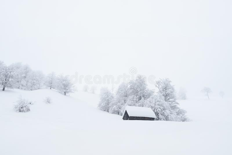 Winter landscape with a mountain house in the snow. Winter landscape with a wooden house in the snow. Snowfall and fog in a mountain village. Privacy in a royalty free stock photos