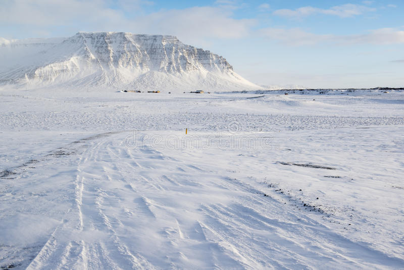 Winter landscape with mountain, a lot of snow and small farm houses, Iceland royalty free stock image