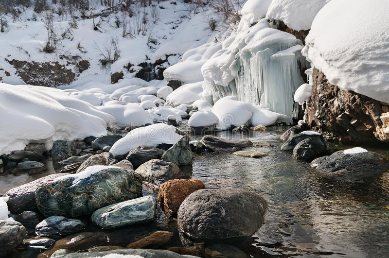 Winter landscape of mountain river with stones and small frozen waterfall.  stock photo