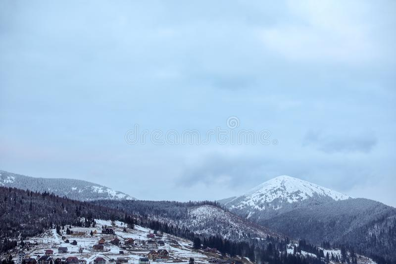 Winter landscape with mountain village near forest. Winter landscape with mountain village near conifer forest stock images
