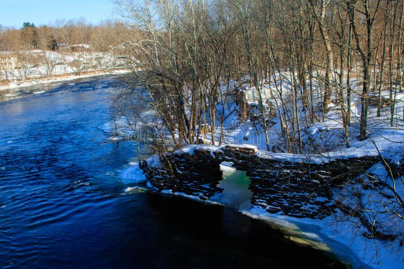 An old stone wall in the river. Winter landscape of an old stone wall in the shade of the trees lining the banks of the Farmington River stock image