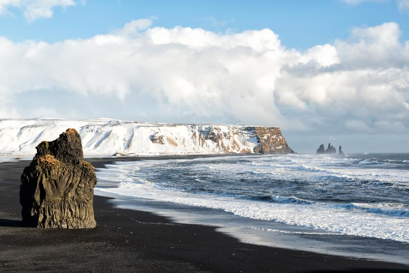 Winter landscape with Reynisdrangar stacks, mountain, black sand beach and ocean waves, Iceland. Winter landscape with Reynisdrangar stacks, snowy mountain royalty free stock photos