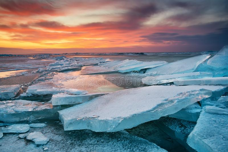 Winter landscape on seashore during sunset. Lofoten islands, Norway. Ice and sunset sky. Natural winter landscape royalty free stock image