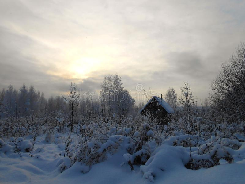 Winter landscape with small house in snowy field. royalty free stock photos