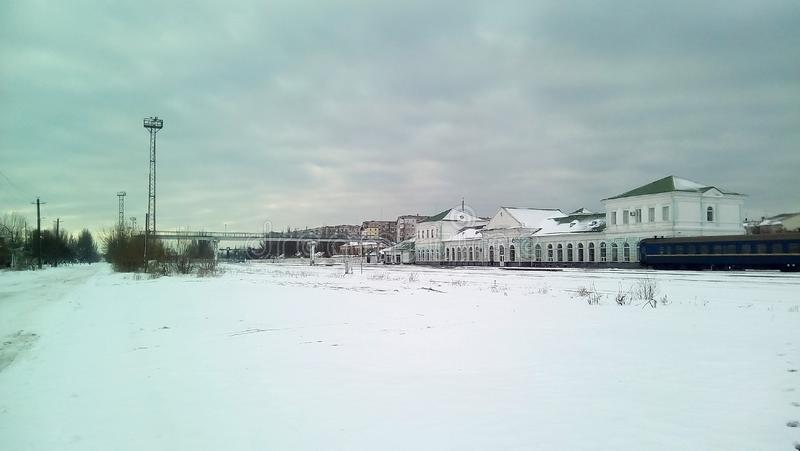 Winter landscape with a small town railway station. The snowy expanse, the light station building on two floors, the last car. royalty free stock photography
