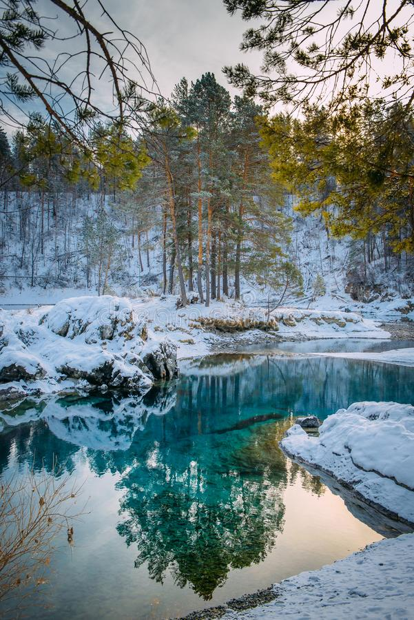 Winter landscape small turquoise lake in the mountains among snow-covered forest. Trees are reflected in the lake water. Vertical stock photos